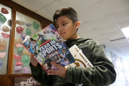 Erick Hernandez, 11, of Lakewood chooses a book during a Bridge of Books Foundation event for sixth graders at Lakewood Middle School in Lakewood, NJ Tuesday, December 18, 2018. The Bridge of Books Foundation, which donates recreational reading books to underprivileged kids across the state, donated its one millionth book during this event.