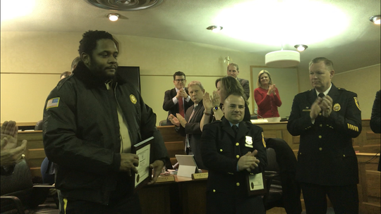 Keith Thornton, left, and Middletown Police Officer Nicholas Manochio, center, are applauded during Monday night's township committeeman for rescuing an elderly woman from a house fire on Saturday night.
