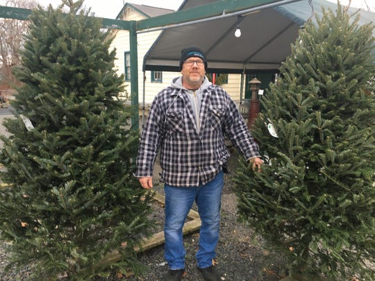 Michael Zajac, owner of The Garden Shoppe on Route 88 in Brick, standing with the last two remaining Christmas trees on his lot on Dec. 17, 2018.