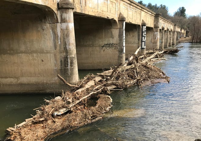 Logs and tree branches often get caught at area bridges, including this jam at the railroad bridge in Asheville's River Arts District.