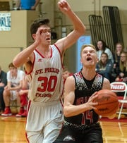 Bellevue Cory Berkimer (14) prepares to drive the basket while St. Philip's Nolan Kersten (30) works on defense.