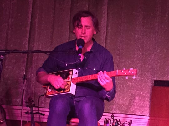 Joe Crookston pulled out a cigar-box guitar as part of his concert in May at Atomic Tom's in Binghamton.