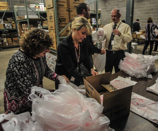Mary Kay Roland, left, superintendent for Johnson City schools, and Kimberly Beukema create bags for the BackPack program in 2014.
