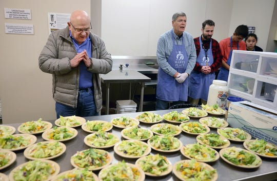 Deacon Bill Hamlin leads the volunteer kitchen staff in prayer before serving meals at Mary's Place, a free meal for the homeless and hungry at Our Lady Star of the Sea Catholic Church in Bremerton.