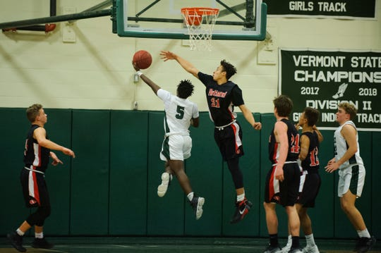Rice's Mo Awayle (5) leaps past Rutland's Jamison Evans (21) for a lay up during the boys basketball game between the Rutland Raiders and the Rice Green Knights at Rice Memorial High School on Monday night December 17, 2018 in South Burlington.