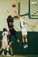 Rutland's Jamison Evans (21) shoots the ball over Rice's John Rousseau (13) during the boys basketball game between the Rutland Raiders and the Rice Green Knights at Rice Memorial High School on Monday night December 17, 2018 in South Burlington.
