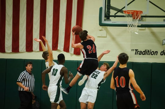 Rutland's Jacob Lorman (24) leaps for a lay up over Rice's Griffin McDermott (22) during the boys basketball game between the Rutland Raiders and the Rice Green Knights at Rice Memorial High School on Monday night December 17, 2018 in South Burlington.