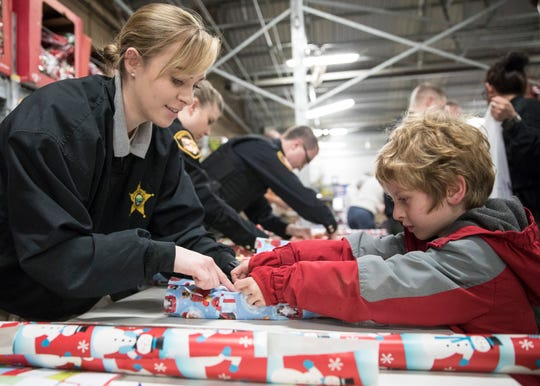 Connor Stamper, right, gets help wrapping presents from Heidi Bray with the Ross County Sheriff's office after his shopping trip with a local officer for the annual Shop with a Cop event at the Chillicothe Walmart on December 17, 2018.