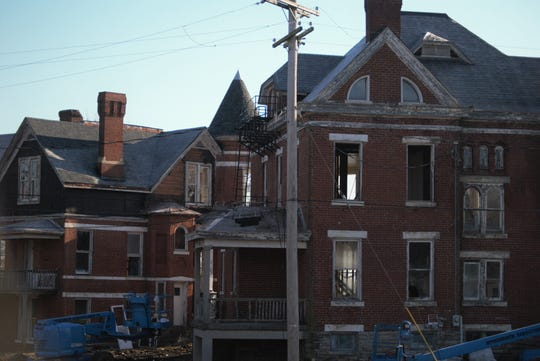 Workers are gutting portions of the interiors of the 14 Queen Anne-style 1890s brick former U.S. Army officer homes Dec. 18, 2018, on Alexander Circle in Fort Thomas as part of a renovation to turn the historic buildings into private residences