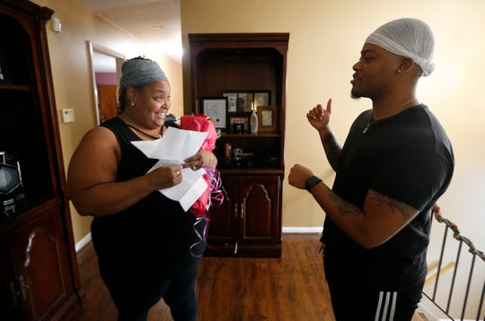 Christina Sanders talks with her oldest son Chris Jr. after he gave her flowers for her birthday Friday, December 7, 2018, at their Forest Park home. Christina and her husband, Christopher have five biological children and adopted six siblings last year. The couple is also fostering two other children.