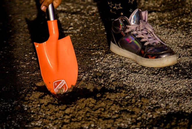 A child digs with a commemorative shovels at the groundbreaking of FC Cincinnati's West End stadium on Tuesday, Dec. 18, 2018, in Cincinnati.