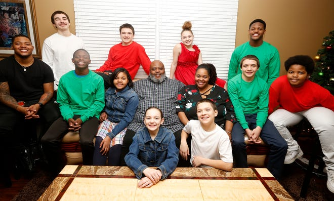 Christopher and Christina Sanders, center, with their eleven children in their Forest Park home. The Sanders have five biological children and adopted six siblings last year. From left; Chris Jr. 21, Caden, 14, Caitlyn 10, Chloe 10, Carson 12, Caleb 15, Chaz, 12. Back row; Coby 17, Christian, 16, Caylee ,14 and Cameron, 15.  Photo shot Friday December 7, 2018.