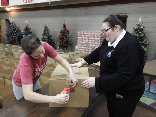 Chrisha Collins tapes a box for Lt. Ariann Maupin as they prepare to load them with food for the Salvation Army's annual holiday food distribution drive.