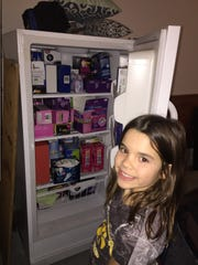 Brenlyn Knutson, 8, stands next to an upright freezer in her family's Johnston home that doubles as a storage device for feminine hygiene products in December 2018. Her mother, Melissa Knutson, started Give Grace, Give Hope in early January 2018, which helps central Iowans get access to pads and tampons.