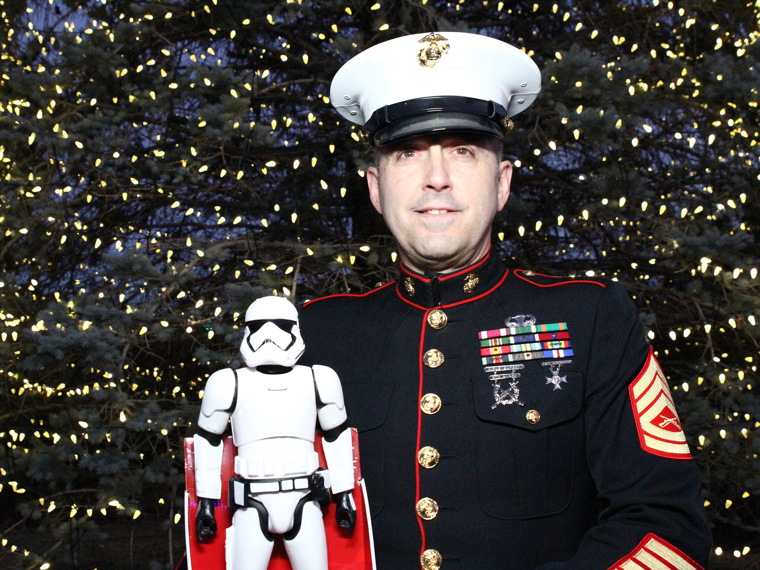 Retired Marine Gunnery Sgt. Mark Amann, current member of the Ankeny Fire Department, holds a stormtrooper toy by the giant tree as gifts are dropped off at Ankeny's fill the truck day during the U.S. Marine Corps Toys for Tots campaign at the Ankeny Fire Station Headquarters on Sunday, Dec. 16, 2018.