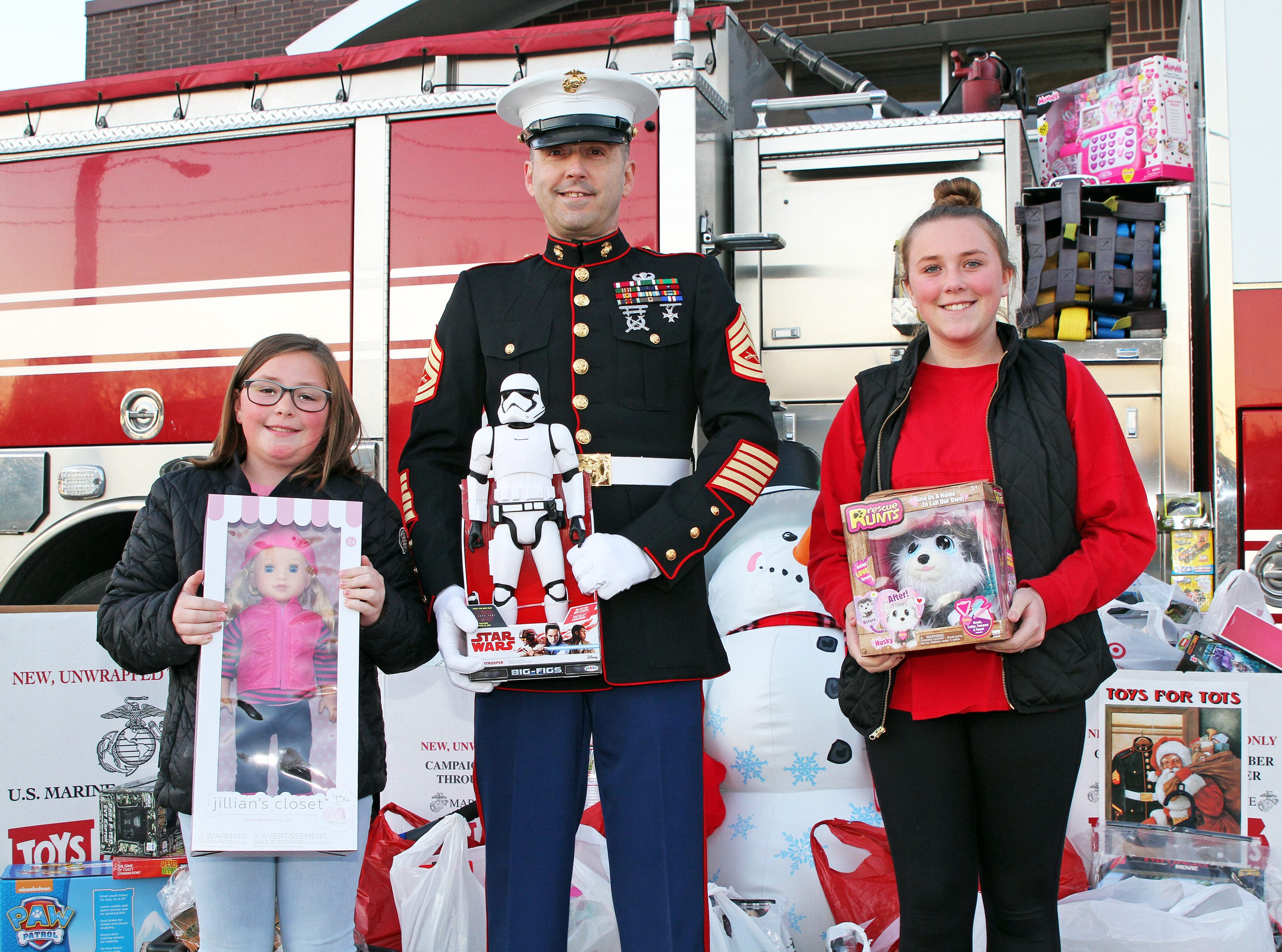 Paisley, 8, and Avery Gavin, 12, of Ankeny help retired Marine Gunnery Sgt. Mark Amann, current member of the Ankeny Fire Department, as gifts are dropped off at Ankeny's fill the truck day during the U.S. Marine Corps Toys for Tots campaign at the Ankeny Fire Station Headquarters on Sunday, Dec. 16, 2018.