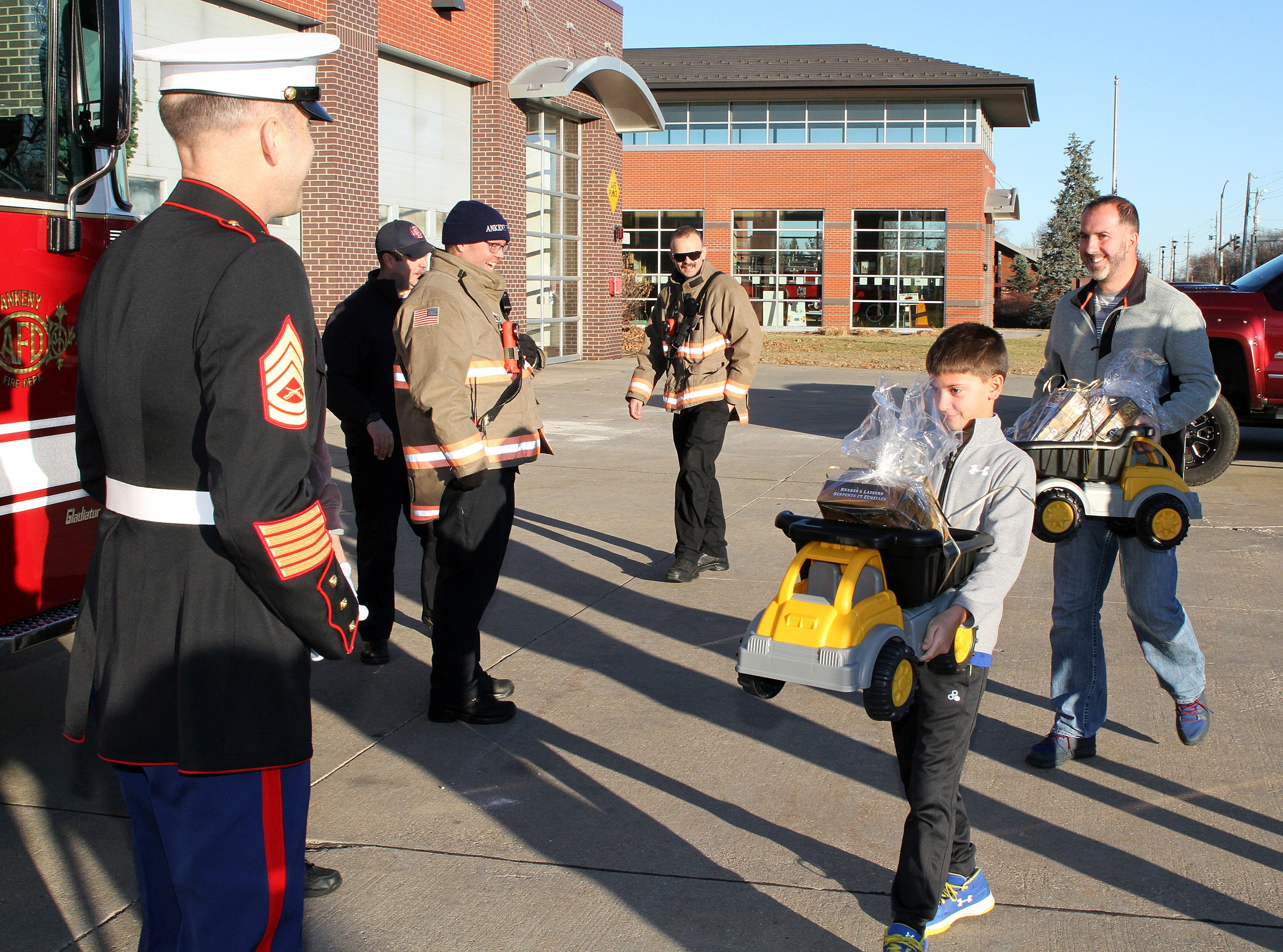 Amel Jusic, 9, of Ankeny delivers a truckload of presents to retired Marine Gunnery Sgt. Mark Amann, current member of the Ankeny Fire Department, as gifts are dropped off at Ankeny's fill the truck day during the U.S. Marine Corps Toys for Tots campaign at the Ankeny Fire Station Headquarters on Sunday, Dec. 16, 2018.