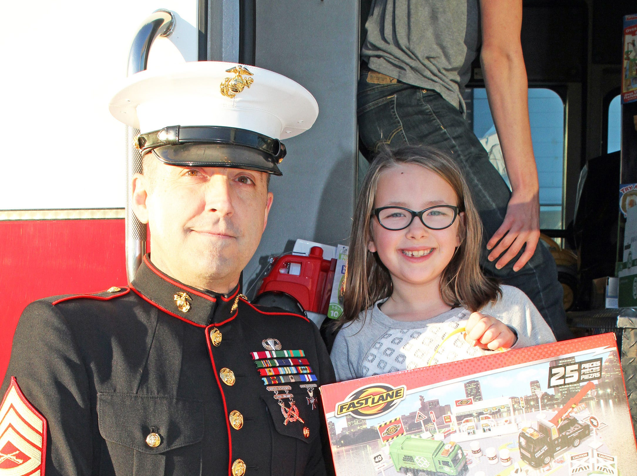 Audrey Dowell, 7, of Ankeny helps retired Marine Gunnery Sgt. Mark Amann, current member of the Ankeny Fire Department, as gifts are dropped off at Ankeny's fill the truck day during the U.S. Marine Corps Toys for Tots campaign at the Ankeny Fire Station Headquarters on Sunday, Dec. 16, 2018.