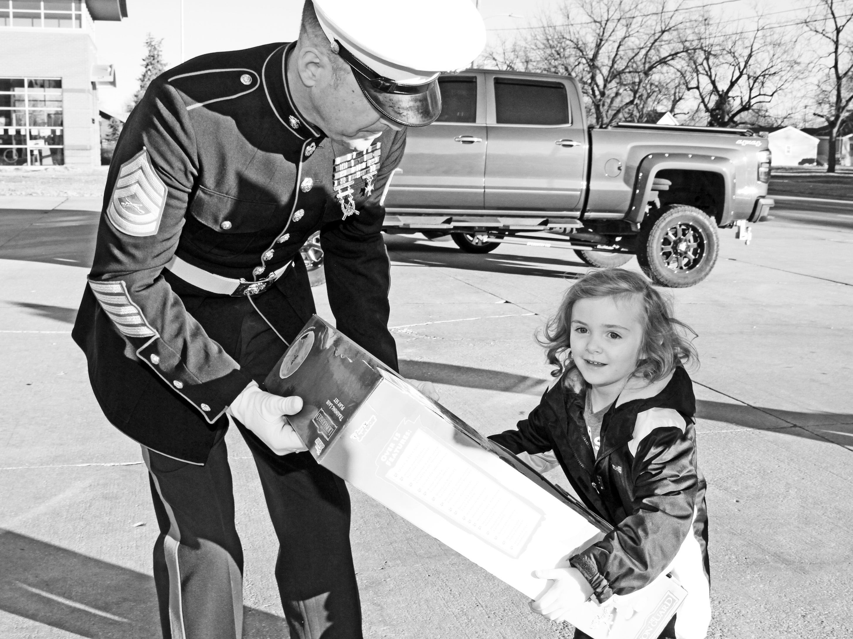 Elizabeth Bonham, 4, of Ankeny delivers presents to retired Marine Gunnery Sgt. Mark Amann, current member of the Ankeny Fire Department, as gifts are dropped off at Ankeny's fill the truck day at the Ankeny Fire Station Headquarters on Sunday, Dec. 16, 2018. The event coincides with the U.S. Marine Corps Toys for Tots campaign.
