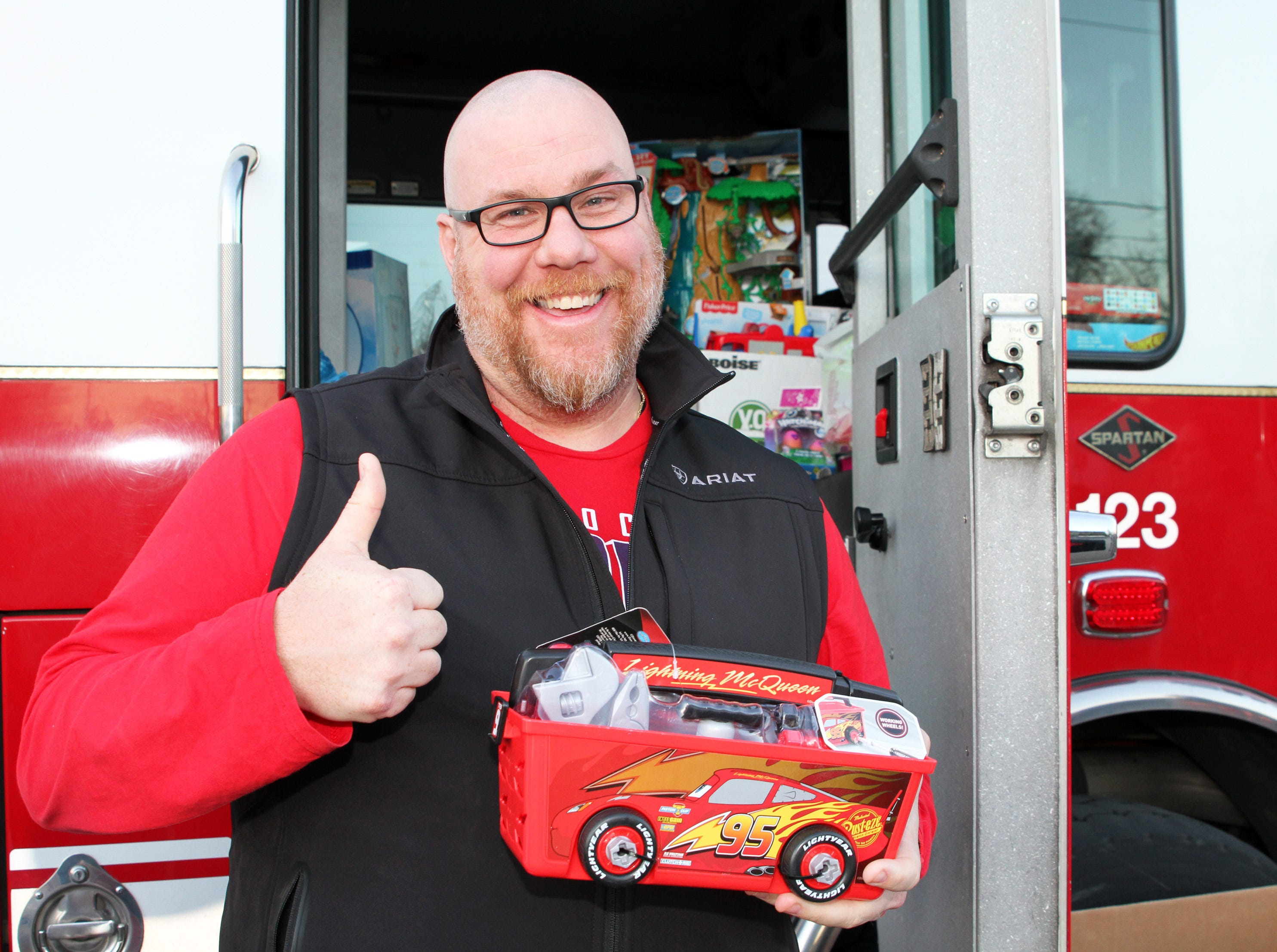 Travis Gavin, 39, of Ankeny donates a present as gifts are dropped off at Ankeny's fill the truck day during the U.S. Marine Corps Toys for Tots campaign at the Ankeny Fire Station Headquarters on Sunday, Dec. 16, 2018.