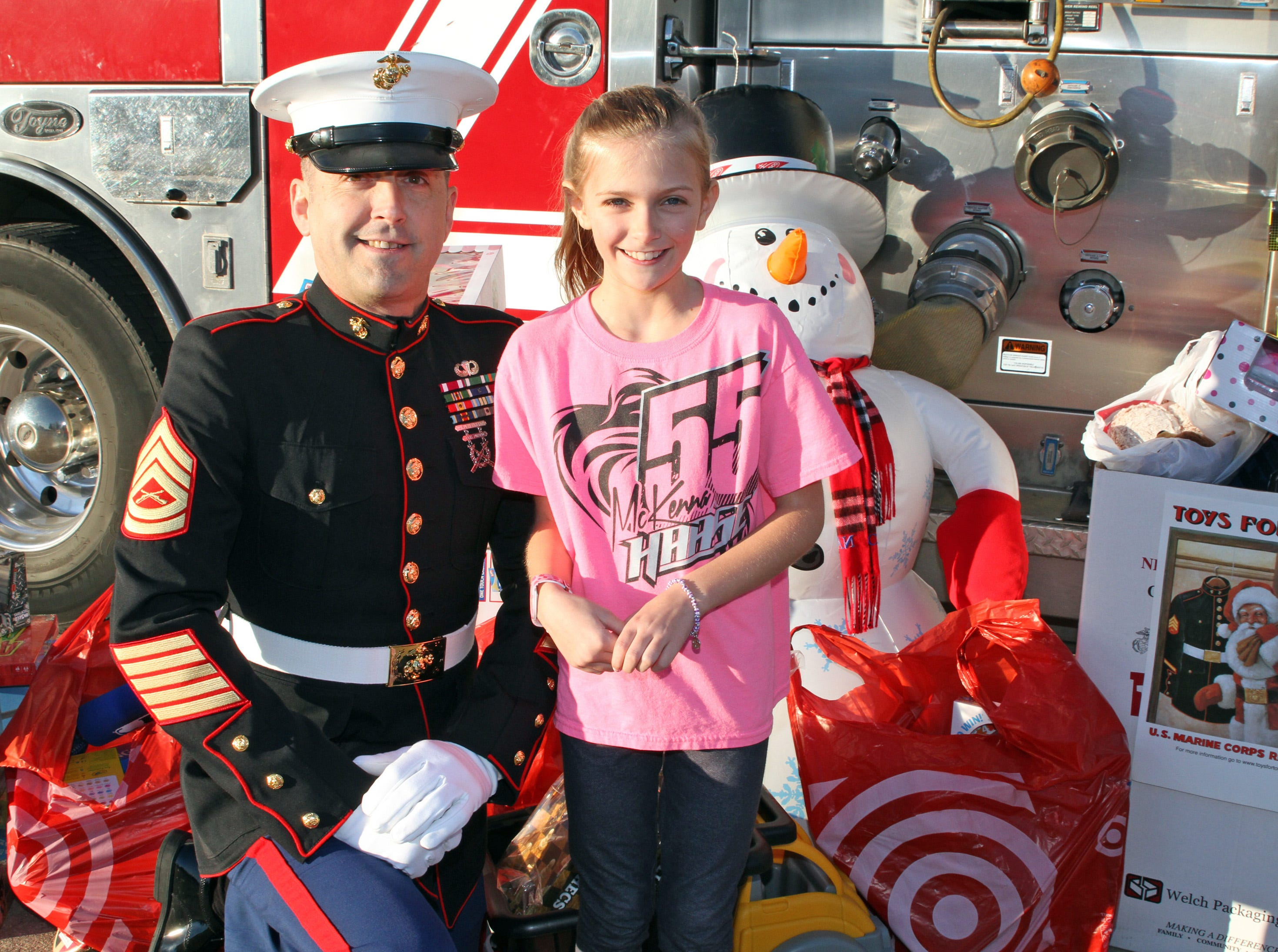 Payton Joynes, 9, of Ankeny stops for a photo with retired Marine Gunnery Sgt. Mark Amann, current member of the Ankeny Fire Department, as gifts are dropped off at Ankeny's fill the truck day. The event coincides with the U.S. Marine Corps Toys for Tots campaign at the Ankeny Fire Station Headquarters on Sunday, Dec. 16, 2018.