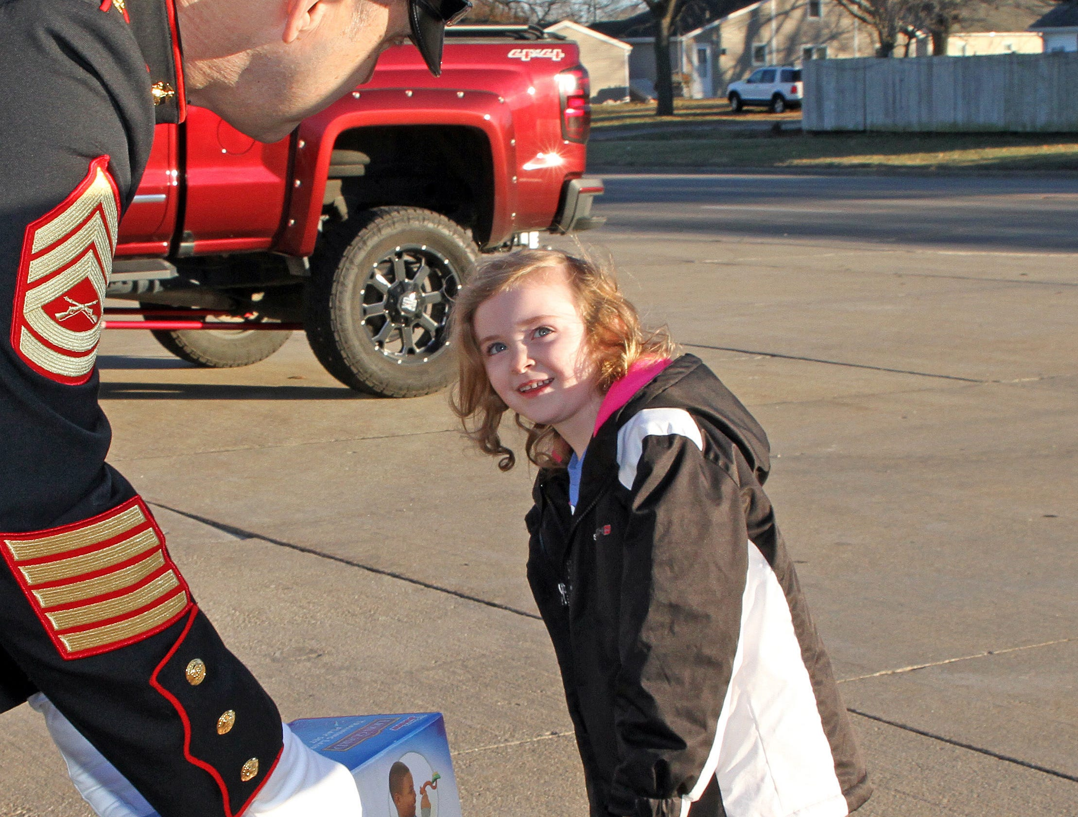 Elizabeth Bonham, 4, of Ankeny delivers presents to Retired Gunnery Sergeant Mark Amann of the U.S. Marines and current member of the Ankeny Fire Department as gifts are dropped off at Ankeny's fill the truck day during the U.S. Marine Corps Toys for Tots campaign at the Ankeny Fire Station Headquarters on Sunday, Dec. 16, 2018.
