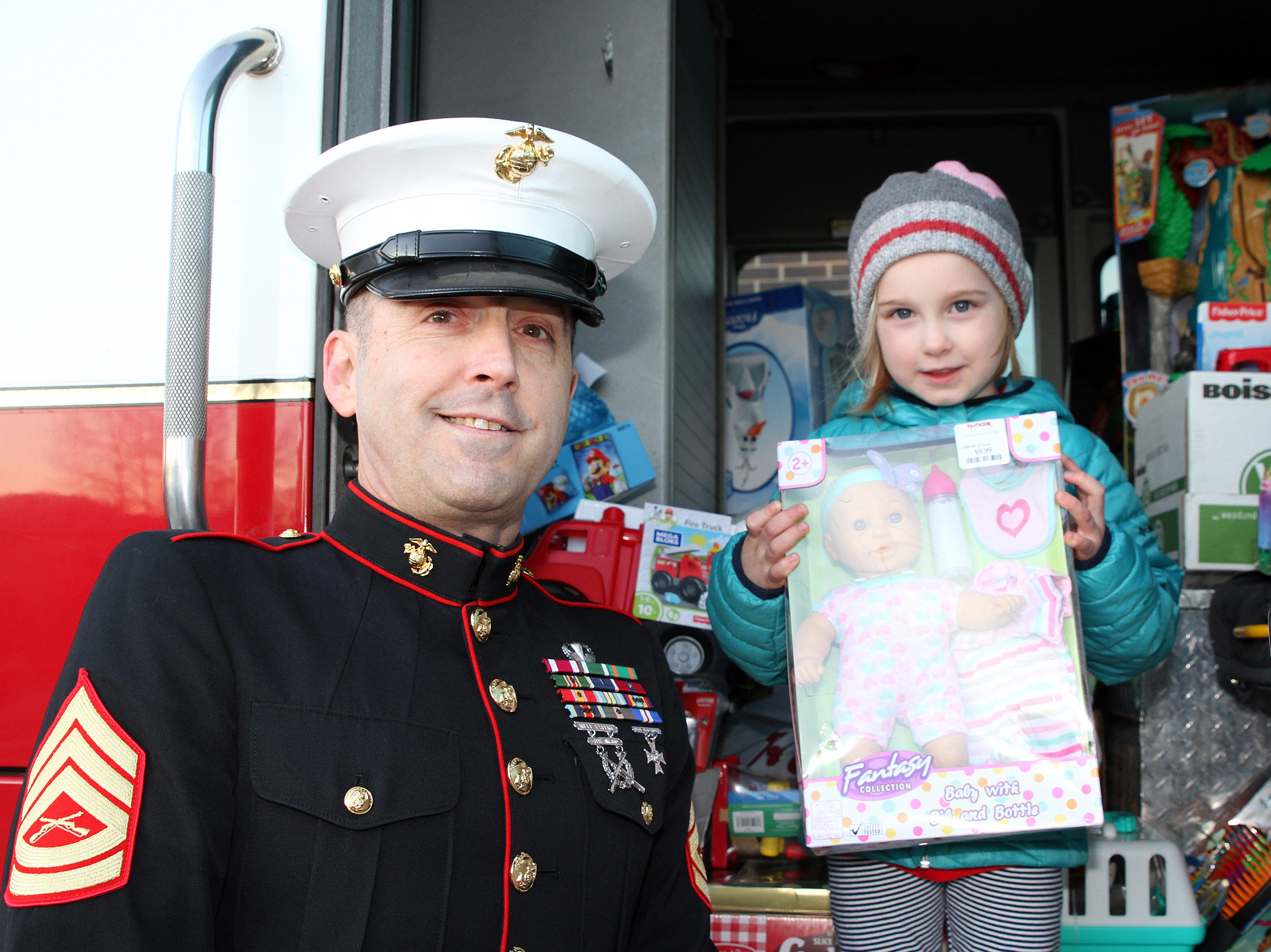 Mackenna Jones, 5, of Polk City helps retired Marine Gunnery Sgt. Mark Amann, current member of the Ankeny Fire Department, as gifts are dropped off at Ankeny's fill the truck day during the U.S. Marine Corps Toys for Tots campaign at the Ankeny Fire Station Headquarters on Sunday, Dec. 16, 2018.