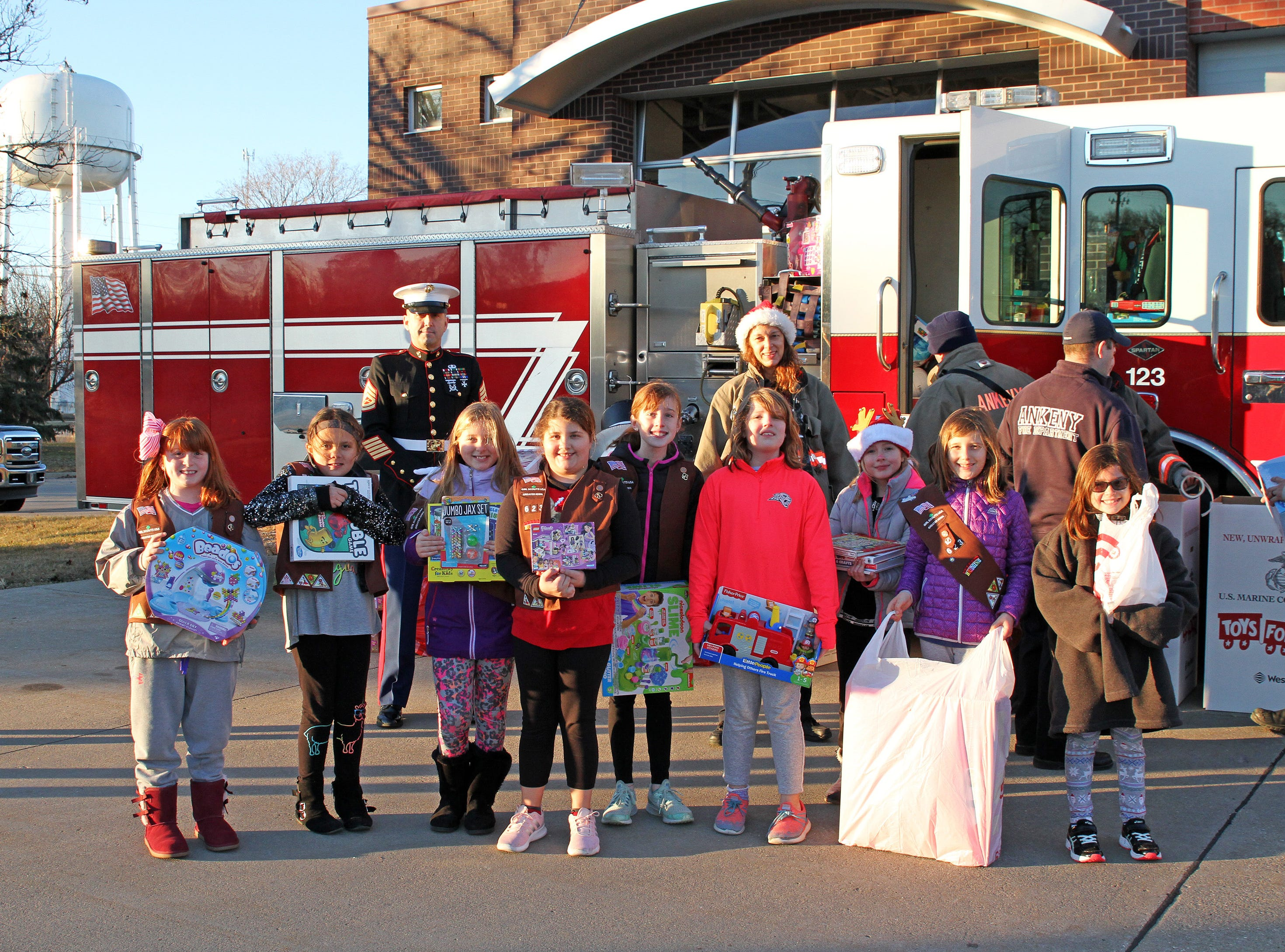 Girl Scout Troop 623 of Ankeny delivers presents during the fill the truck day during the U.S. Marine Corps Toys for Tots campaign at the Ankeny Fire Station Headquarters on Sunday, Dec. 16, 2018.