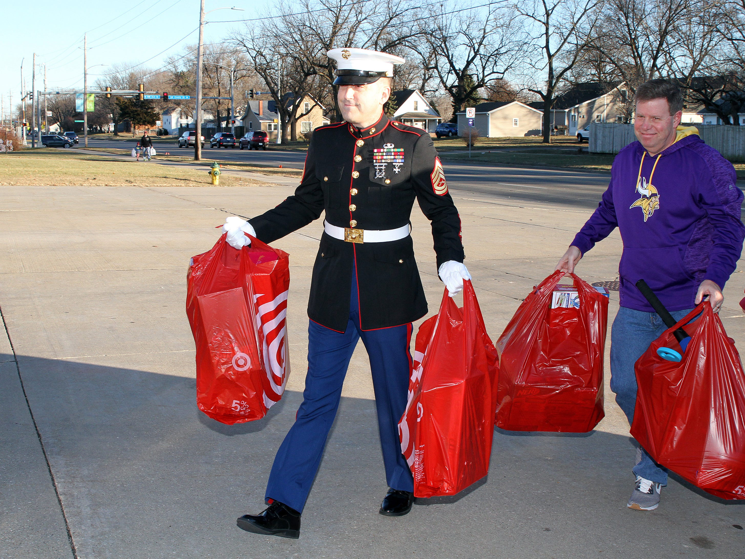 Retired Marine Gunnery Sgt. Mark Amann, current member of the Ankeny Fire Department, carries gifts as they are dropped off at Ankeny's fill the truck day during the U.S. Marine Corps Toys for Tots campaign at the Ankeny Fire Station Headquarters on Sunday, Dec. 16, 2018.