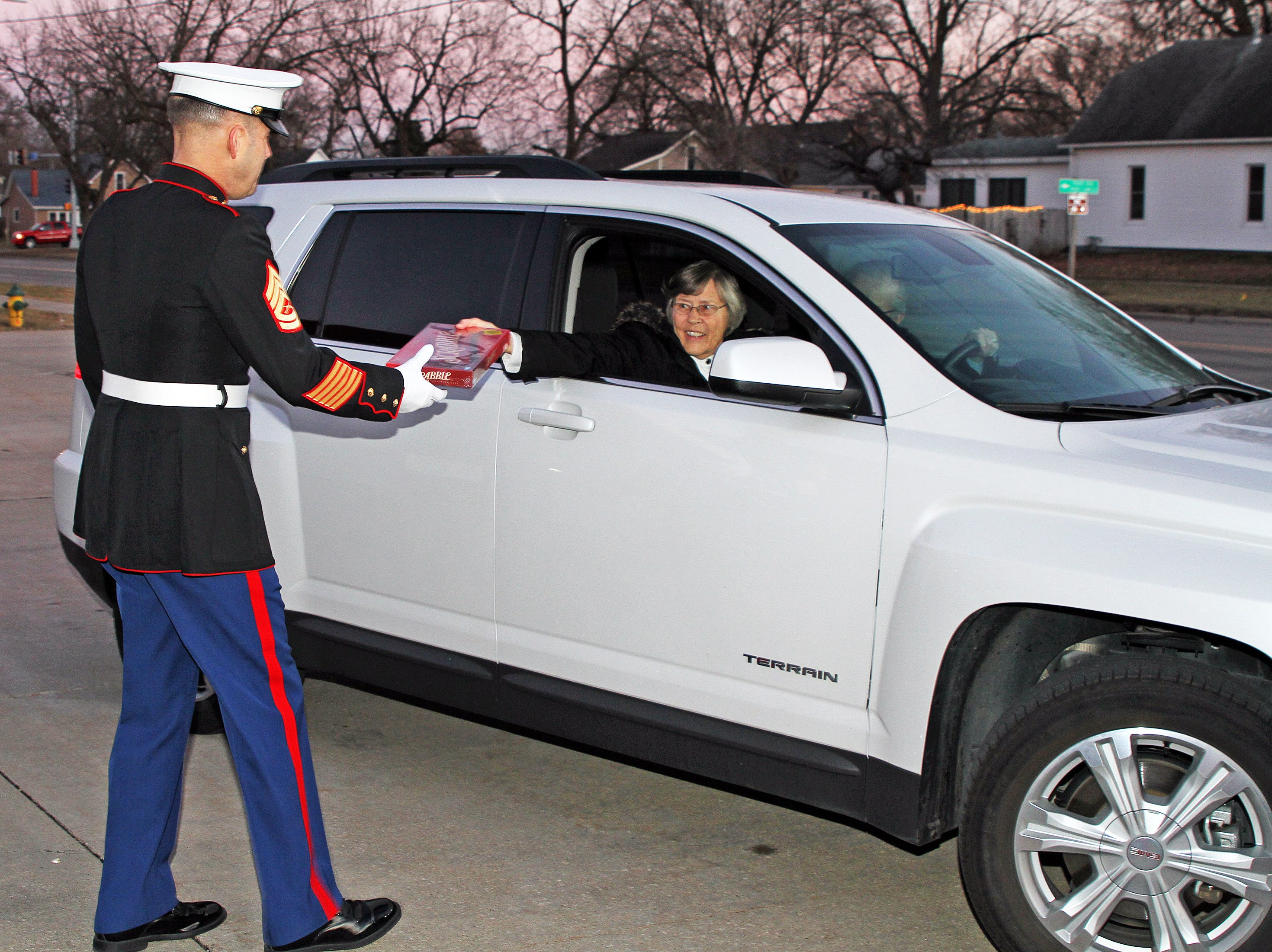 Retired Marine Gunnery Sgt. Mark Amann, current member of the Ankeny Fire Department, greets people as gifts are dropped off at Ankeny's fill the truck day during the U.S. Marine Corps Toys for Tots campaign at the Ankeny Fire Station Headquarters on Sunday, Dec. 16, 2018.