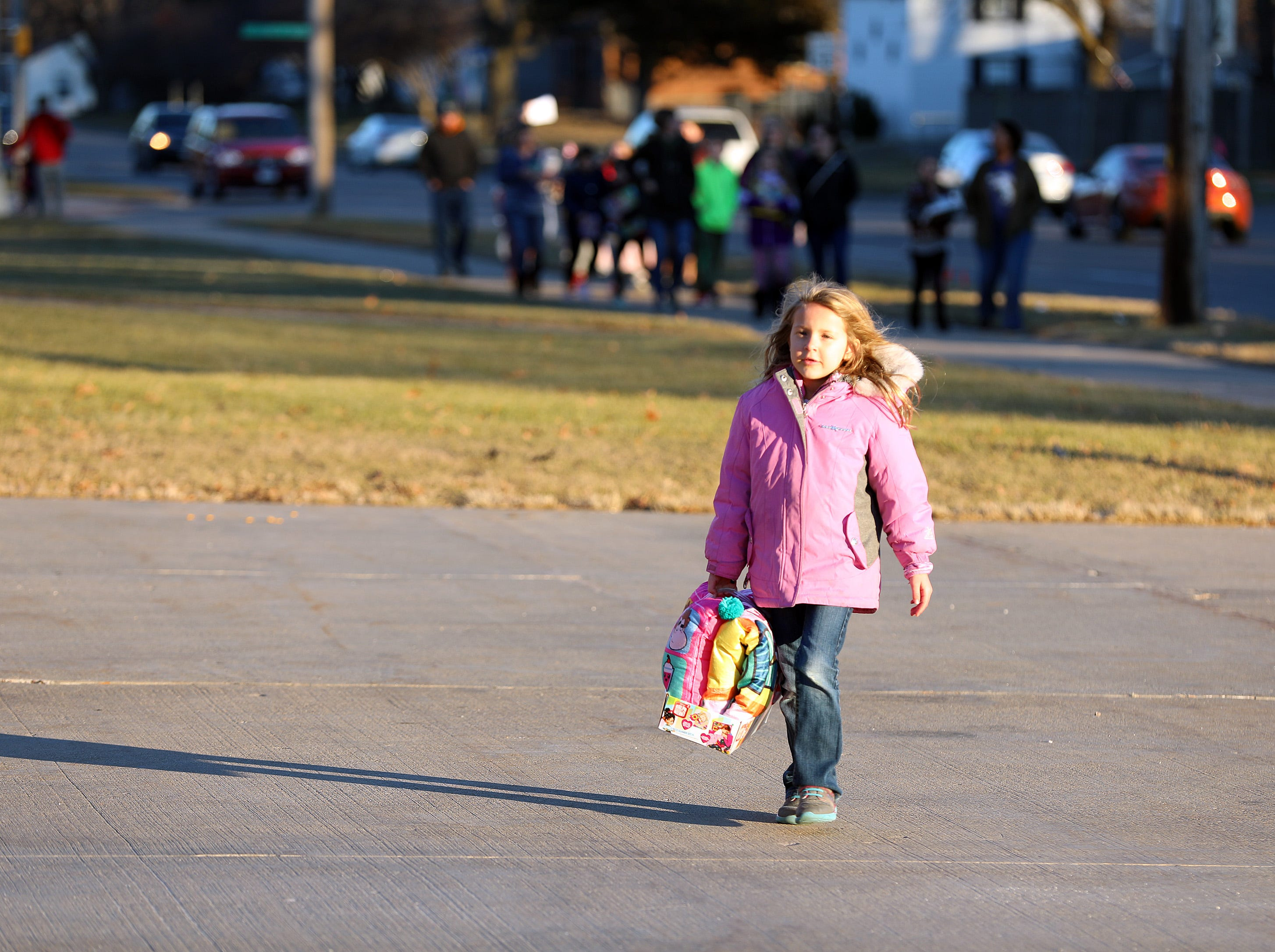 Katelyn Norgaard, 6, of Ankeny brings a present as gifts are dropped off at Ankeny's fill the truck day during the U.S. Marine Corps Toys for Tots campaign at the Ankeny Fire Station Headquarters on Sunday, Dec. 16, 2018.