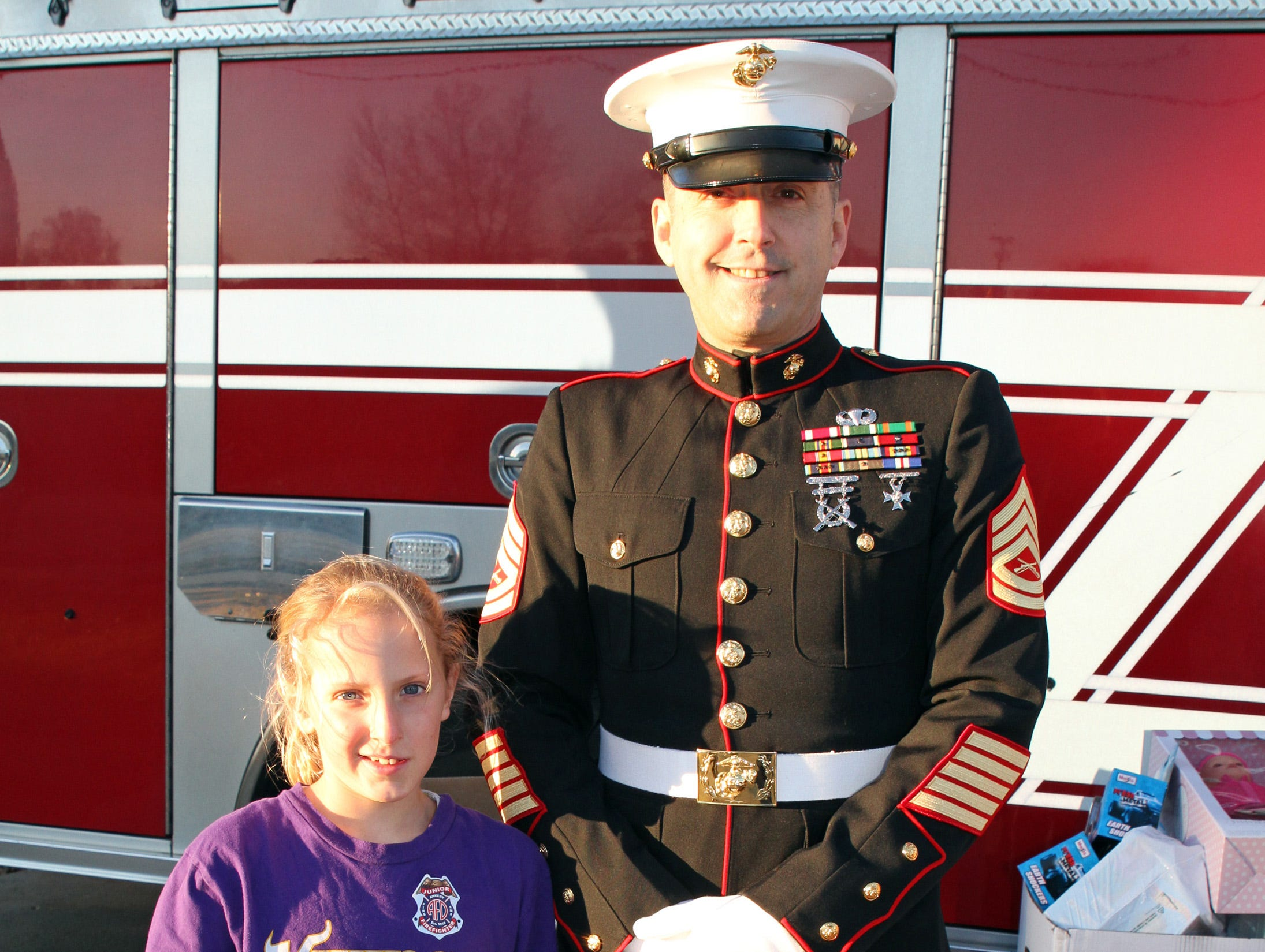 Kendra Norgaard, 10, of Ankeny helps retired Marine Gunnery Sgt. Mark Amann, current member of the Ankeny Fire Department, as gifts are dropped off at Ankeny's fill the truck day during the U.S. Marine Corps Toys for Tots campaign at the Ankeny Fire Station Headquarters on Sunday, Dec. 16, 2018.