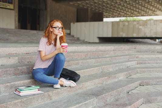 Thoughtful Student Girl Sitting With Coffee Cup Outdoors