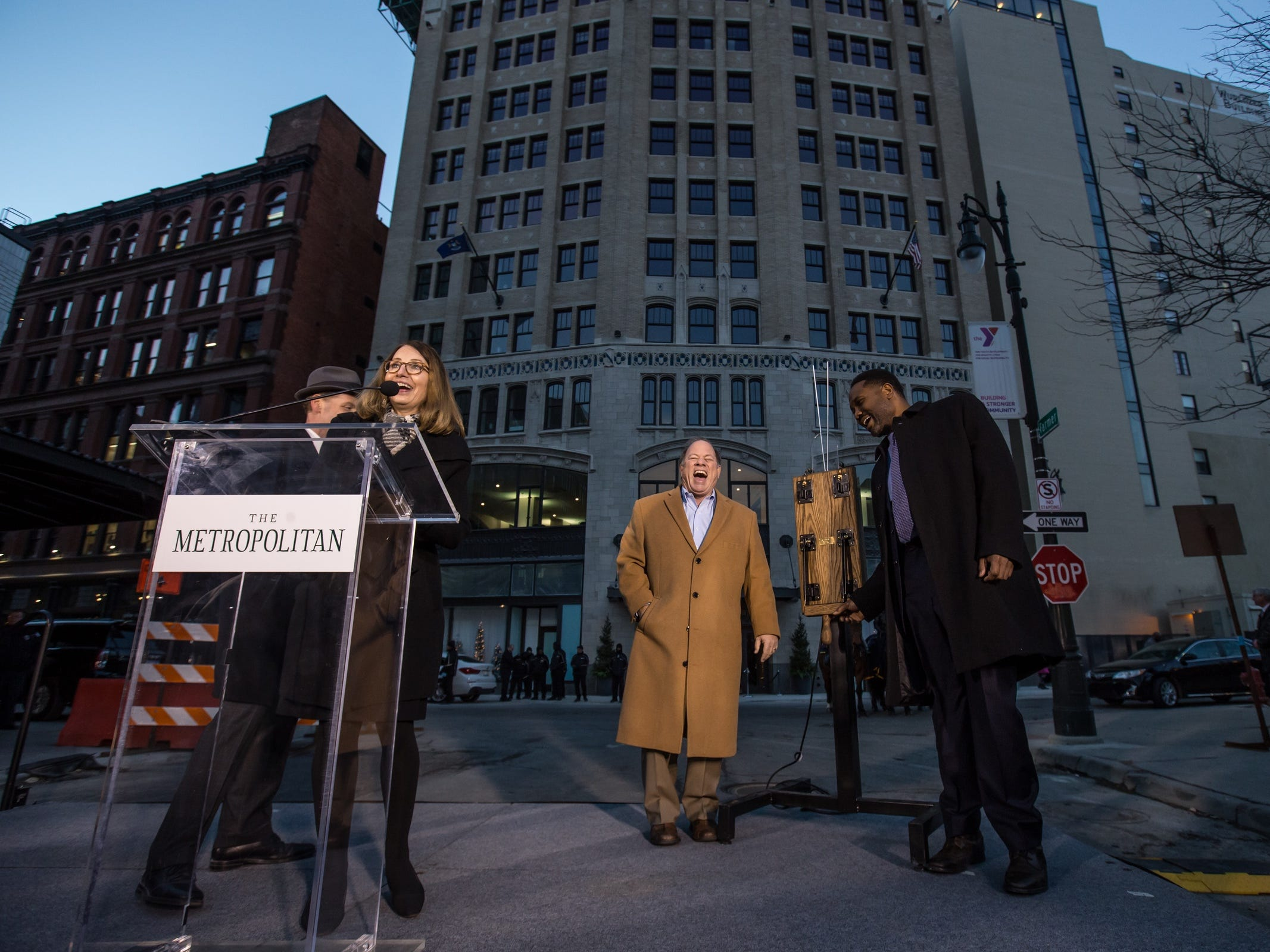 Roxbury Group founder and principal Stacy Fox speaks on the mic as Detroit Mayor Mike Duggan and Means Group CEO Eric Means share a laugh before the lighting ceremony during a public dedication of the historic Metropolitan Building in downtown Detroit.
