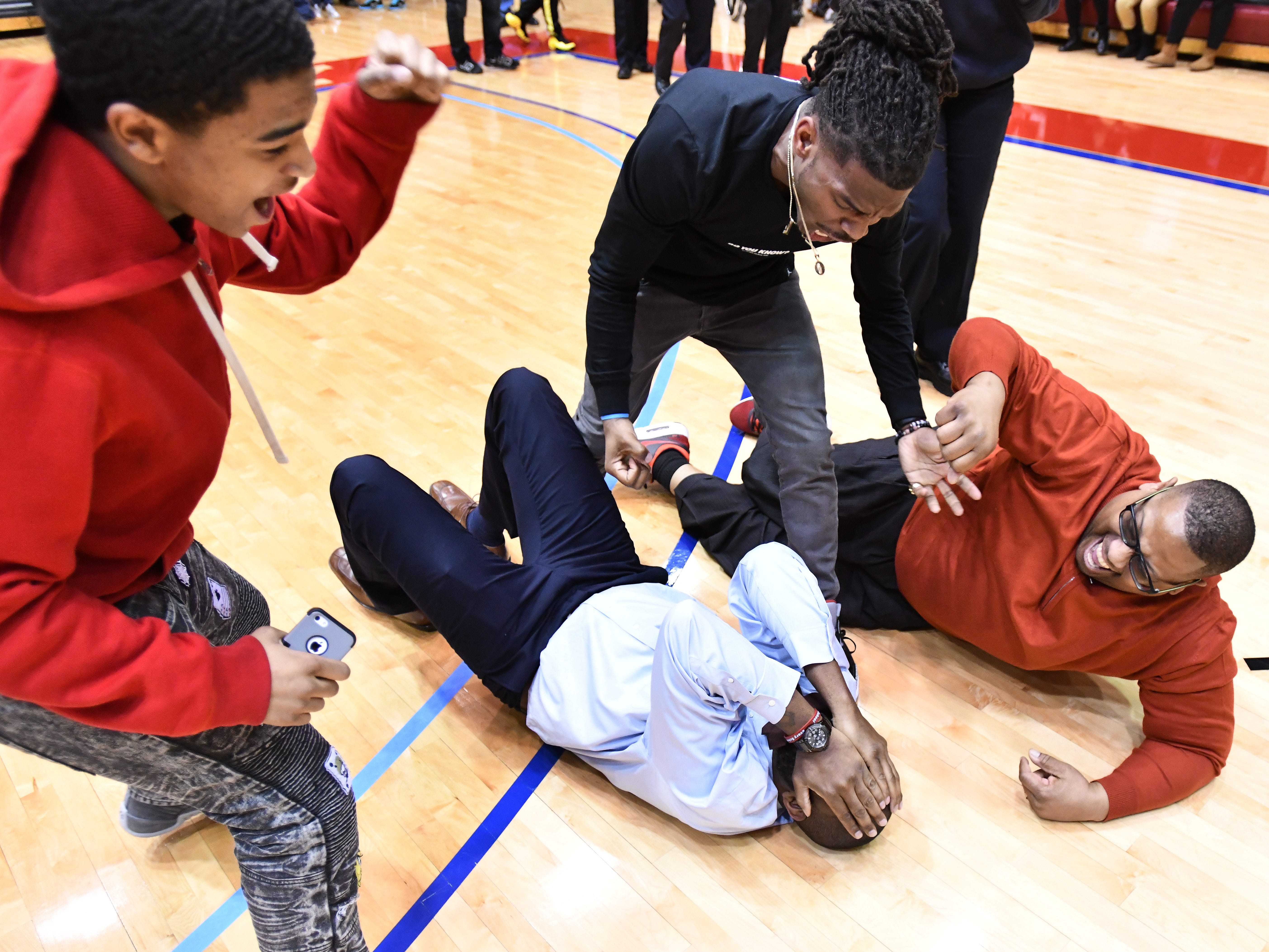 Mumford girls basketball coach Kareem Hogan covers his face and lays on the floor, tackled by parents, friends and family after his team's championship victory over Renaissance in PSL final.