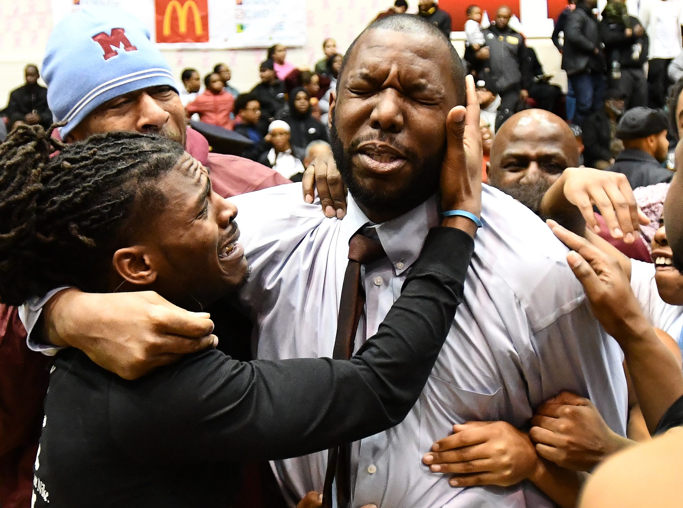 Mumford girls basketball coach Kareem Hogan is mobbed by players, parents, friends and family after the team's PSL championship victory. Mumford rallied from a 10-point halftime deficit to beat Renaissance 60-58.