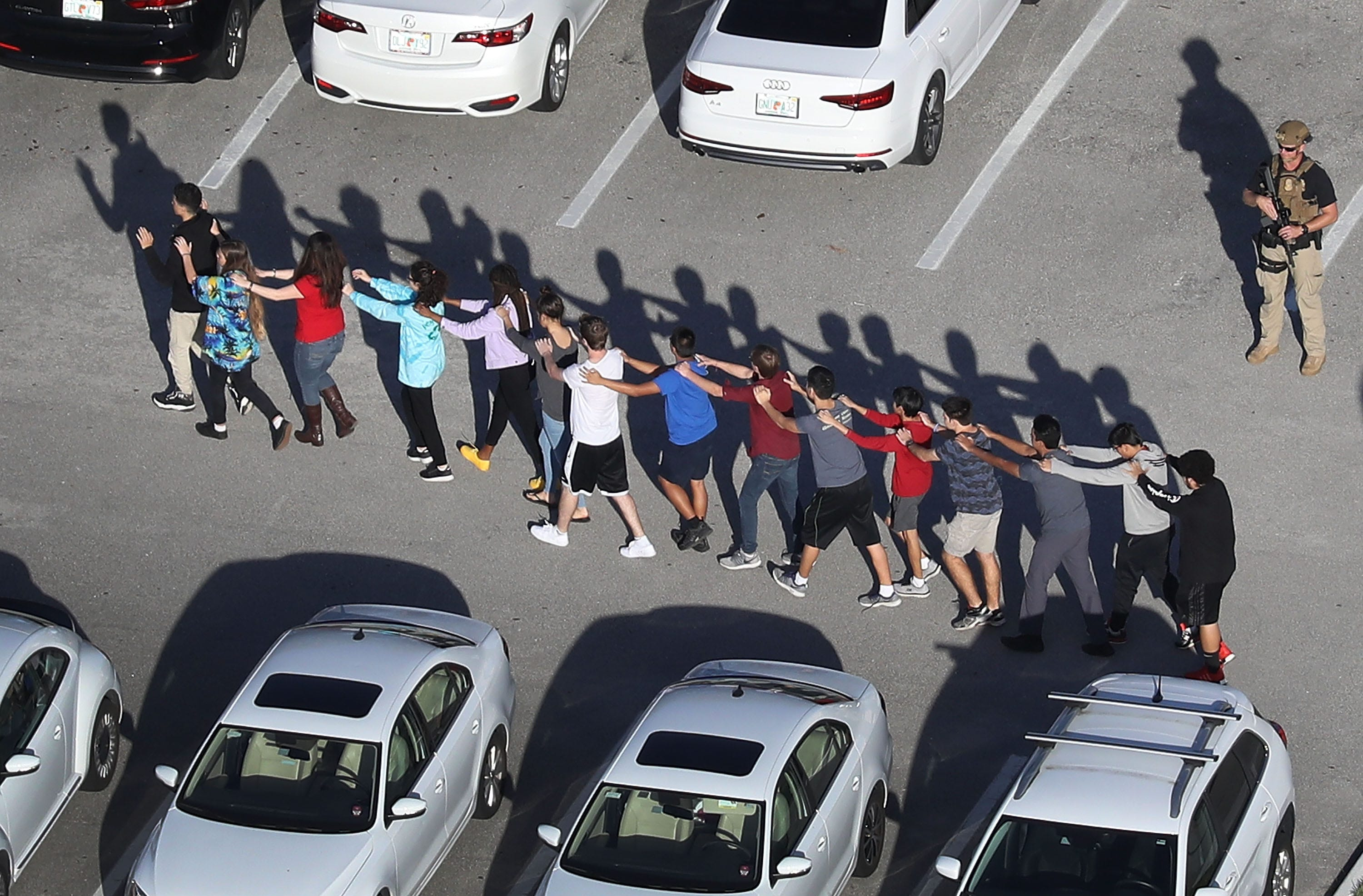 People are brought out of the Marjory Stoneman Douglas High School after a shooting at the school on February 14, 2018, in Parkland, Florida.