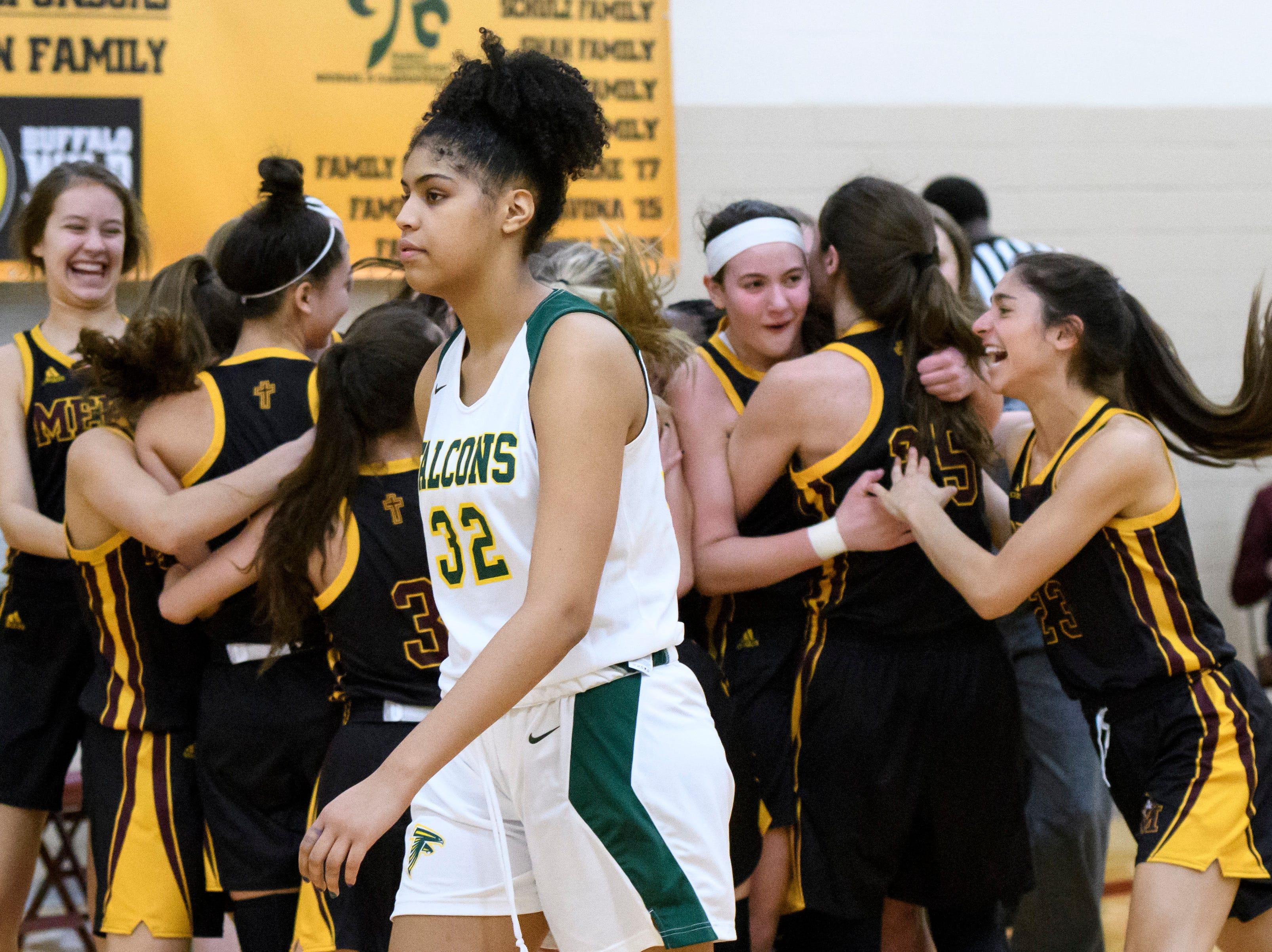 Birmingham Groves' Jasmine Worthy walks past the celebrating Farmington Mercy team after losing a big game at Farmington Mercy High School on February 26, 2018.