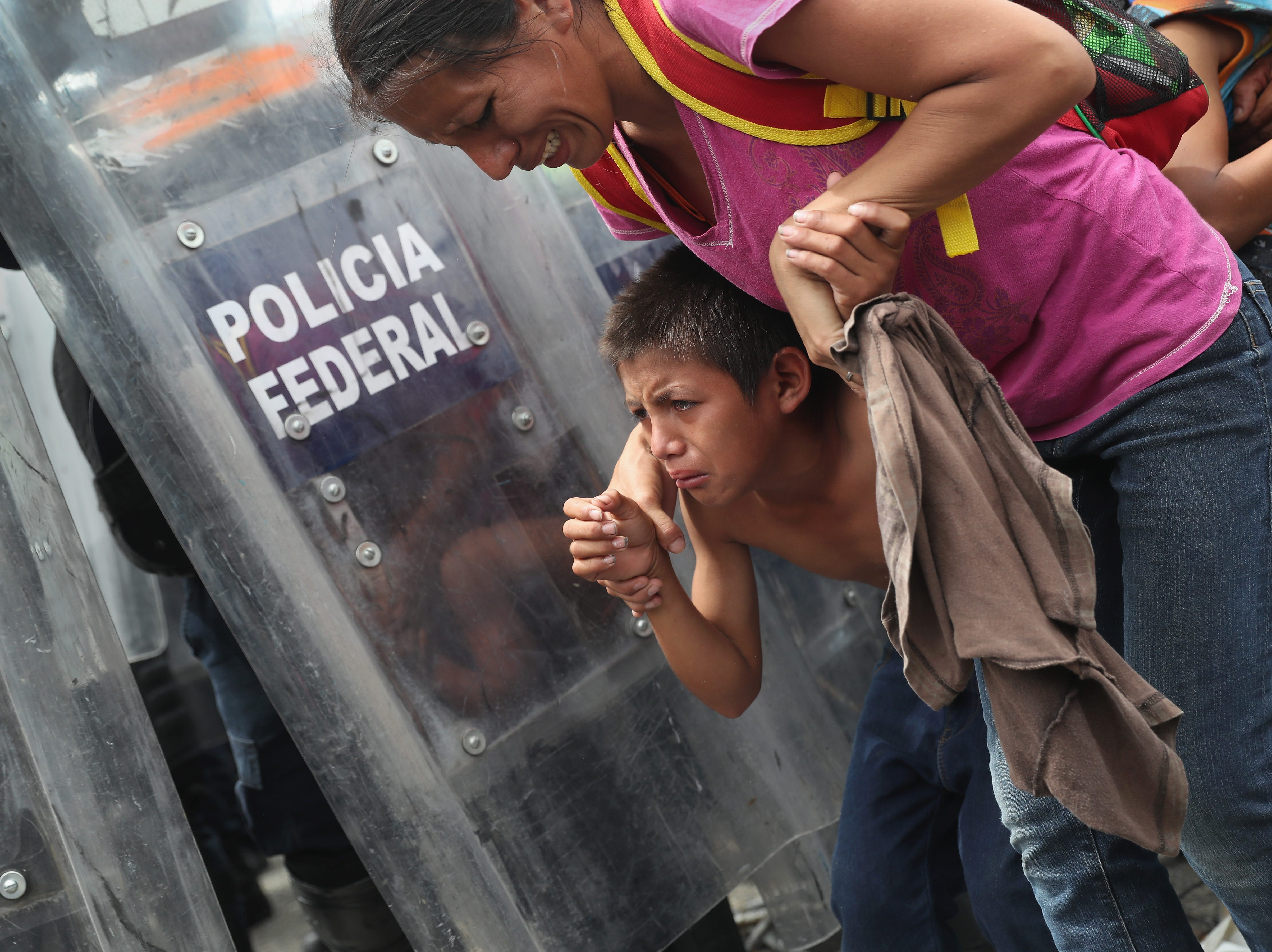 A child takes cover as Mexican riot police clash with the migrant caravan on the border of Mexico and Guatemala on October 19, 2018, in Ciudad Tecun Uman, Guatemala. The caravan opened the gate into Mexico but was pushed back by Mexican riot police. Some immigrants threw stones at the police who then fired tear gas into the crowd.