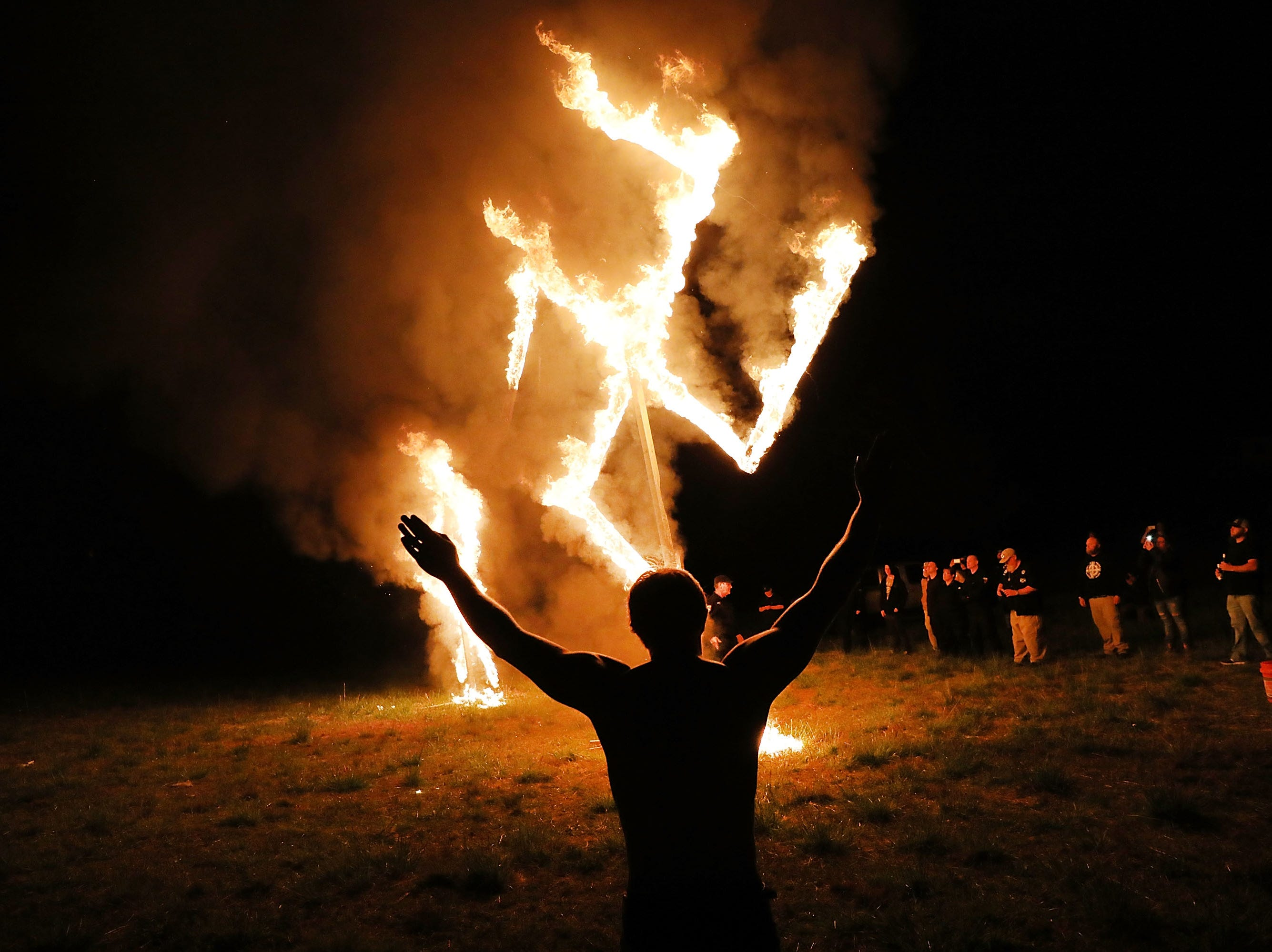 Members  of the National Socialist Movement, one of the largest neo-Nazi groups in the U.S., burn a swastika after a rally on April 21, 2018, in Draketown, Georgia. Community members had opposed the rally in Newnan and came out to embrace racial unity in the small Georgia town. Fearing a repeat of the violence that broke out after Charlottesville, hundreds of police officers were stationed in the town during the rally in an attempt to keep the anti racist protesters and neo-Nazi groups separated.