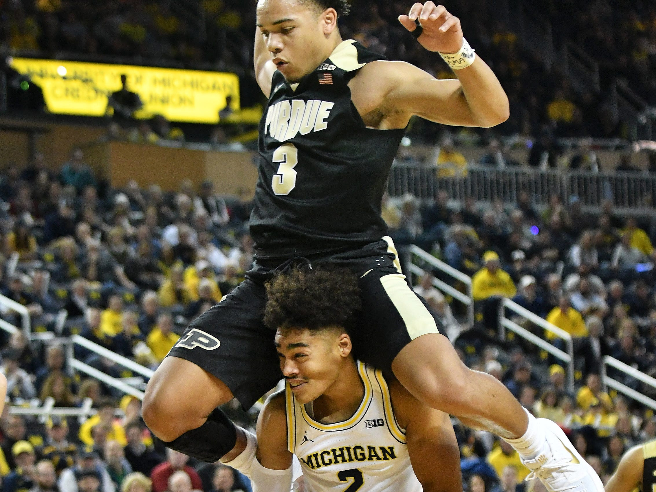 Purdue guard Carsen Edwards (3) goes flying over Michigan guard Jordan Poole (2) during a game at Crisler Center in Ann Arbor, Michigan. on Jan. 9, 2018. Michigan had a spectacular 2017-18 season, winning the Big Ten tournament and advancing the NCAA tournament final before losing to champion Villanova.