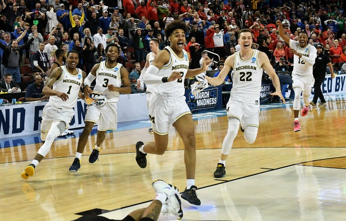 In what was possibly the state of Michigan's biggest sports moment of 2018, Michigan guard Jordan Poole, center, and his Wolverines teammates celebrate his game-winning shot against Houston in the second round of the Men's NCAA Tournament in Wichita, Kansas on March 17, 2018. Michigan won 64-63 and would advance all the way to the NCAA championship game, losing to Villanova.