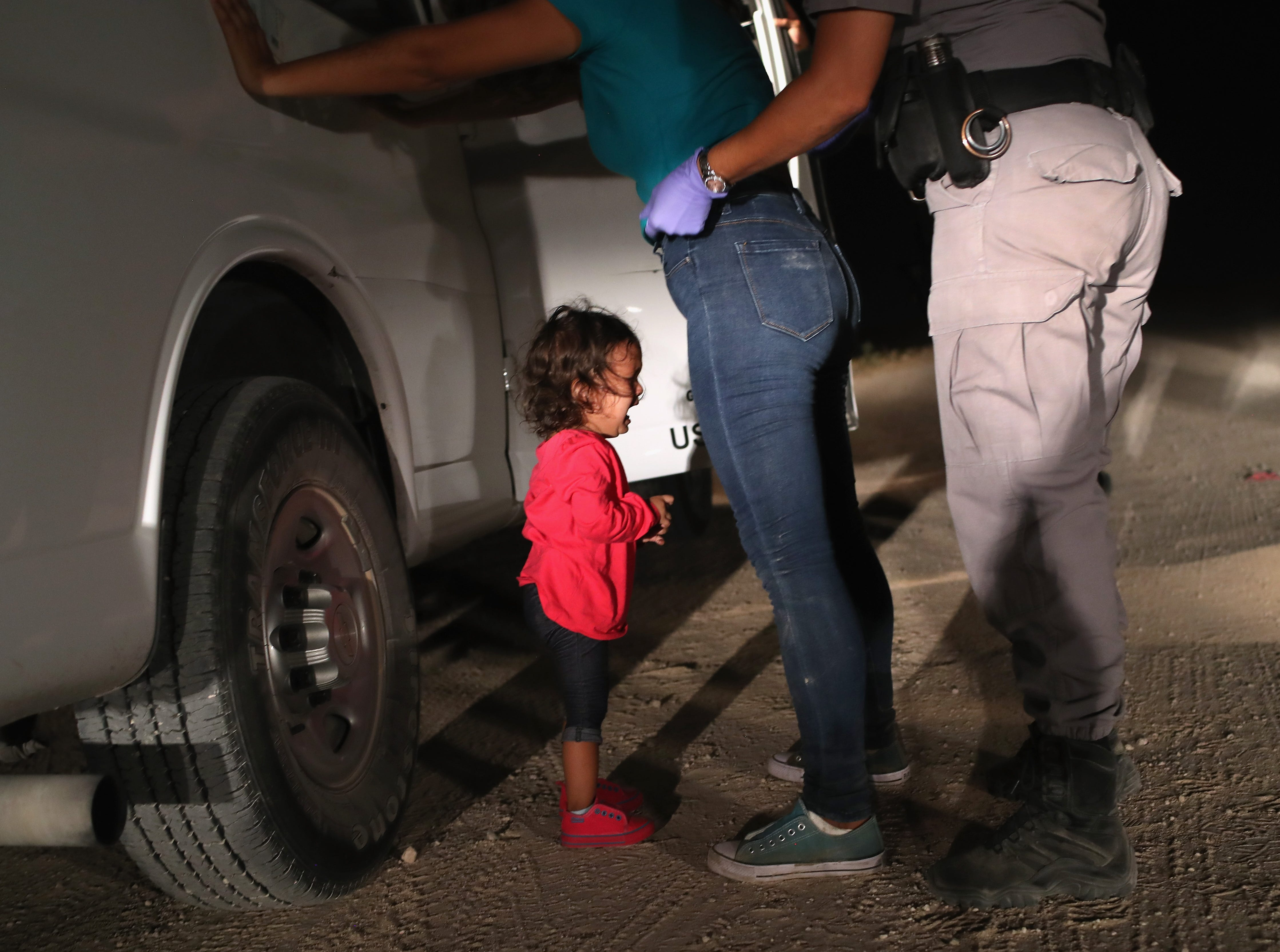 A 2-year-old Honduran asylum seeker cries as her mother is searched and detained near the U.S.-Mexico border on June 12, 2018, in McAllen, Texas. The asylum seekers had rafted across the Rio Grande from Mexico and were detained by U.S. Border Patrol agents before being sent to a processing center for possible separation.