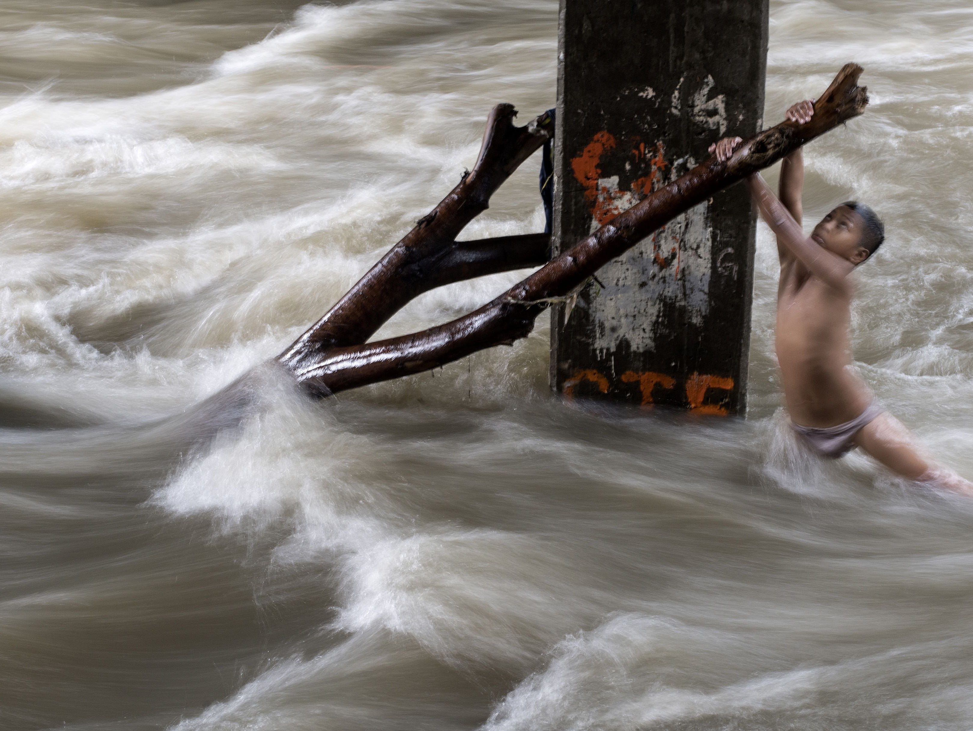 A boy holds a partially submerged branch as he plays in a swollen river caused by heavy rains under a bridge in Manila on June 11, 2018.