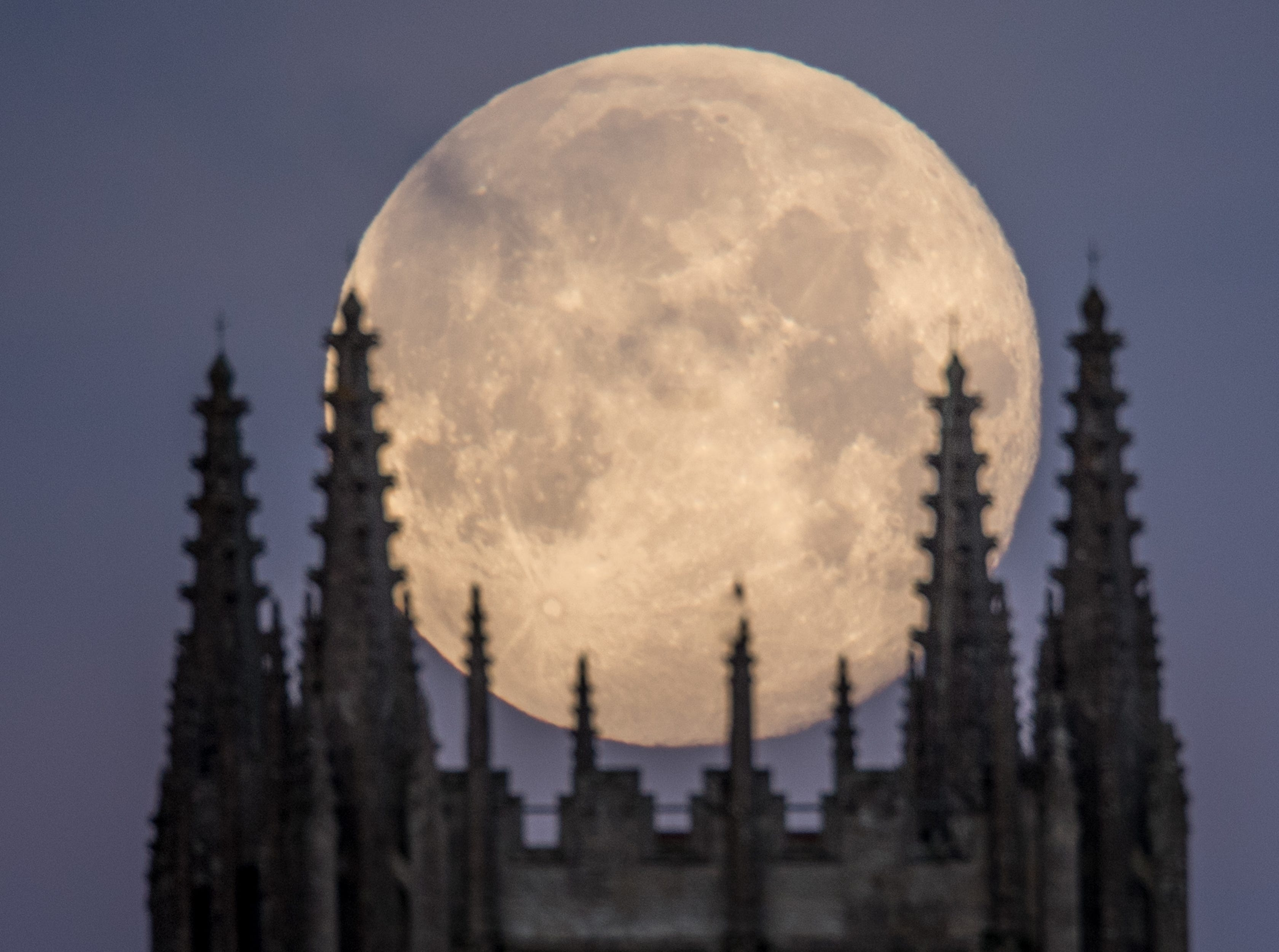 A Super Blue Blood Moon sets behind Downside Abbey, a Benedictine monastery, in Stratton-on-the-Fosse on Feb. 1, 2018, in Somerset, England. It was the second full moon in January, close to its nearest point to Earth on its orbit, and was totally eclipsed by the Earth's shadow. The last time these events coincided was in 1866.
