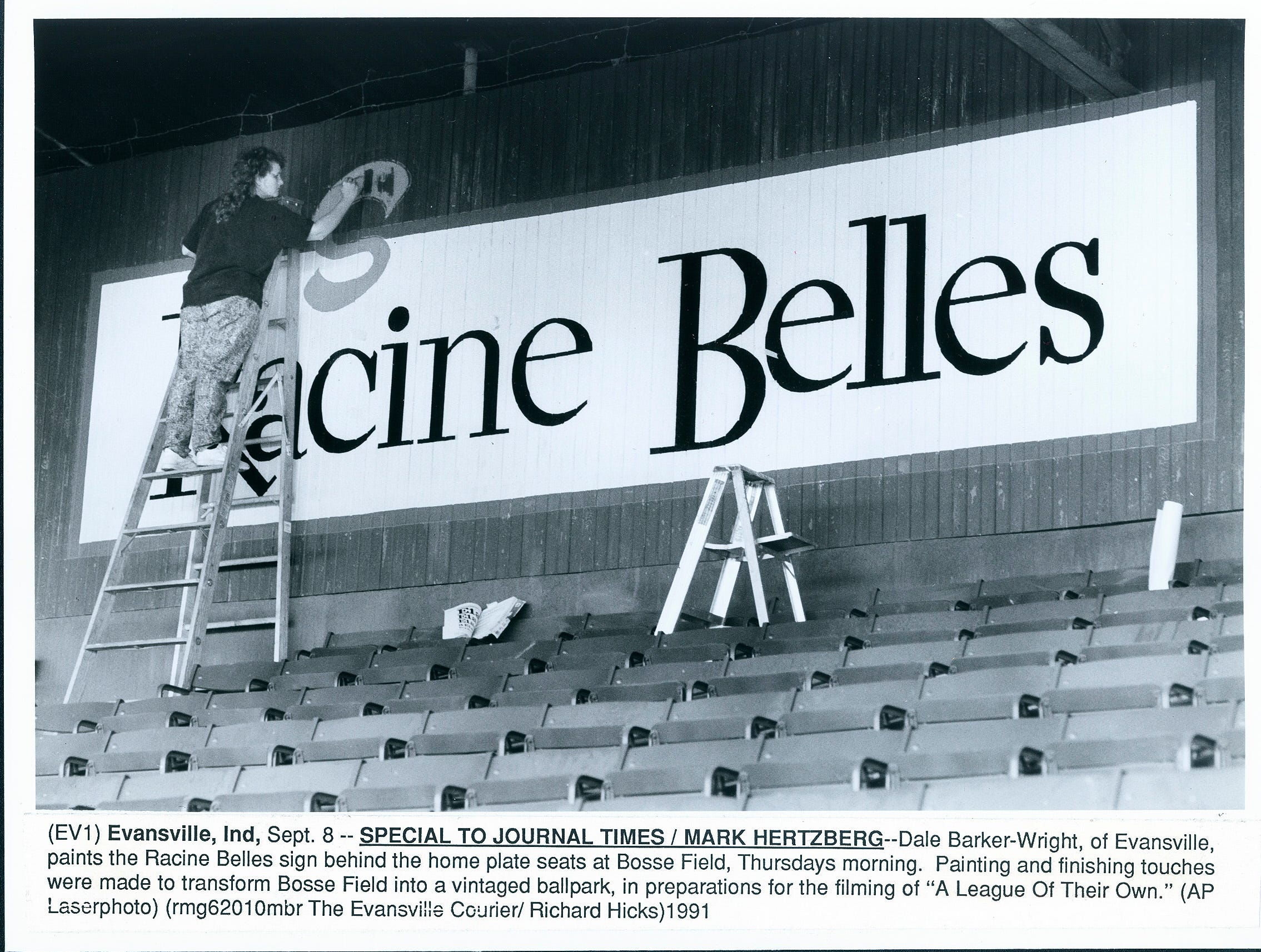 Dale Barker-Wright of Evansville paints the Racine Belles sign behind home plate at Bosse Field in Evansville, Indiana.
