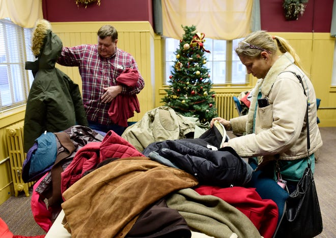 Tina Dyson of Lindsey, right, and Todd Burden of Oak Harbor check out coats at a coat giveaway held at Pontifex by the Fremont Ross High School Teen Leadership Corps.