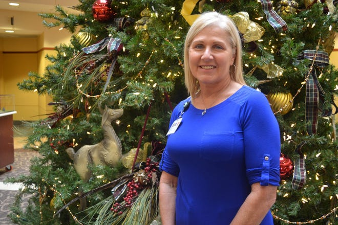 "Lavin Schwan poses by the Christmas tree on display at The Bellevue Hospital, where she works. Schwan presents ""Joey's Story"" to school, businesses and organizations in an effort to educate people about drug addiction and to inspire compassion for those entrapped by it."