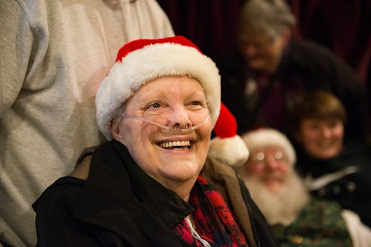 Glenda Seitz smiles as she sits for a photo with family as they visit Santa Claus in Old Town Square on Wednesday, December 12, 2018. Glenda, in hospice care after four years of cancer, had never sat on Santa's lap.