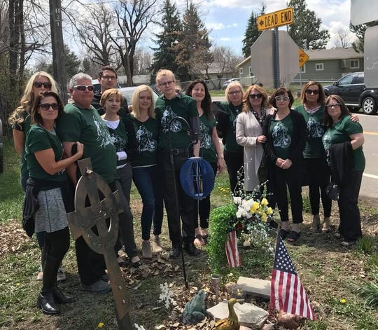Family and friends of the late Austin Sherwood meet at a roadside memorial.